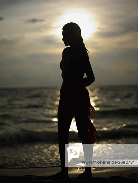 Silhouette of a young woman standing on the beach