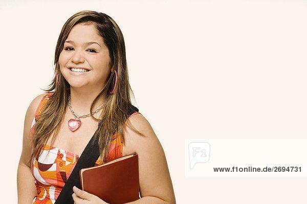 Portrait einer jungen Frau hält ein Tagebuch und lächelnd