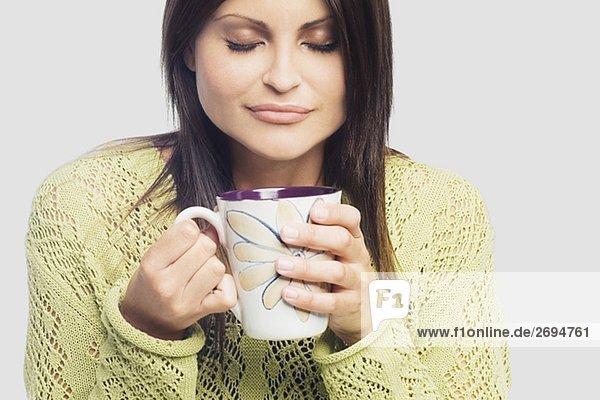 Nahaufnahme of a junge Frau hält eine Tasse Kaffee