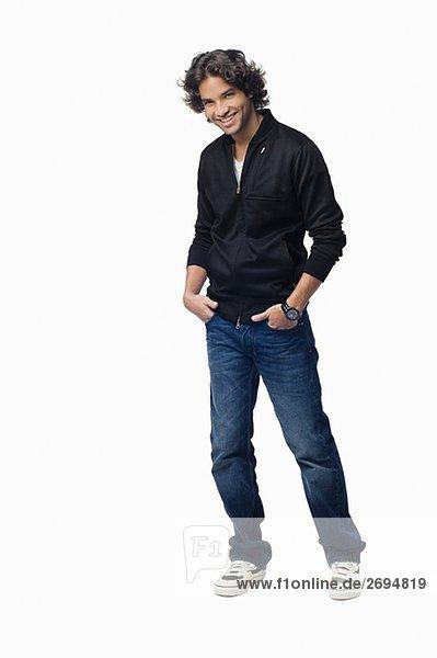 Porträt eines jungen Mannes stehen mit den Händen in seine Taschen und lächelnd