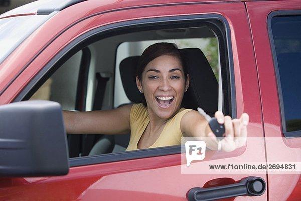 Portrait einer jungen Frau in einem Auto sitzt und zeigen einen Autoschlüssel