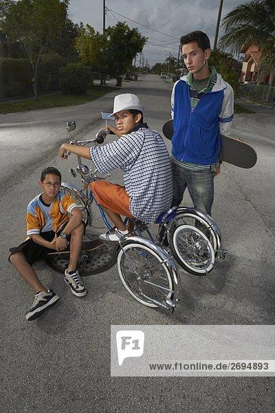 Auf einem low rider Fahrrad mit seinen beiden Freunden neben ihm ein Teenager Porträt