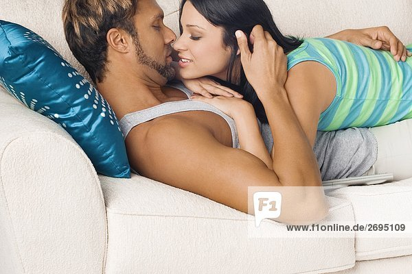 Side profile of a couple romancing on a couch