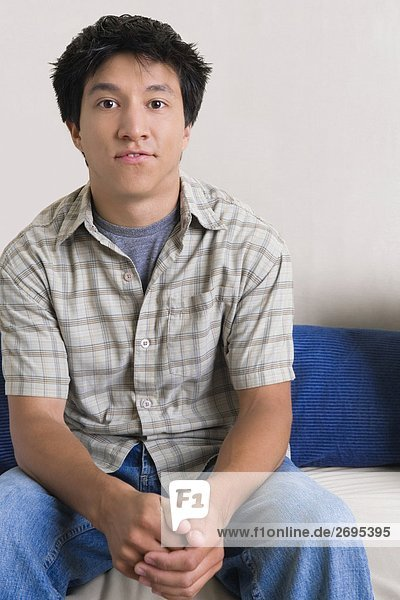 Portrait of a young man sitting on a couch