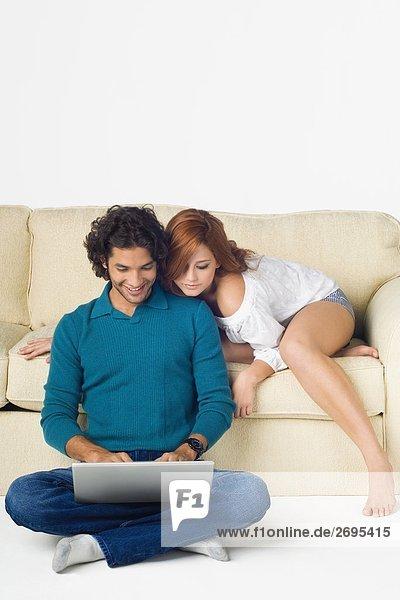 Junger Mann mit einem Laptop mit einer jungen Frau stützte sich über ihn