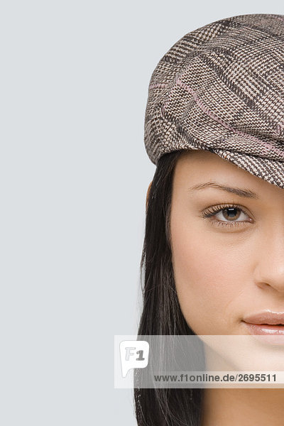 Portrait of a young woman wearing a flat cap