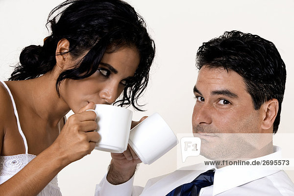 Close-up of a young woman and a mid adult man drinking coffee