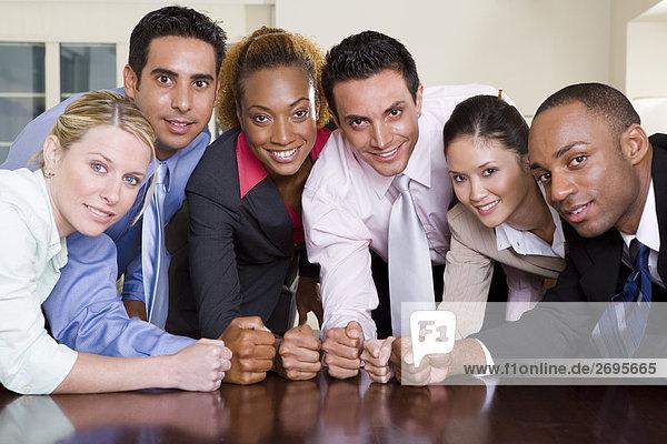 Portrait einer Gruppe von Führungskräften stampfenden ihren Fäusten auf einen Konferenztisch