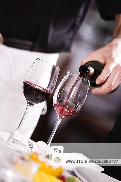 Mitte Schnittansicht eines Mannes Gießen Rotwein in ein Weinglas