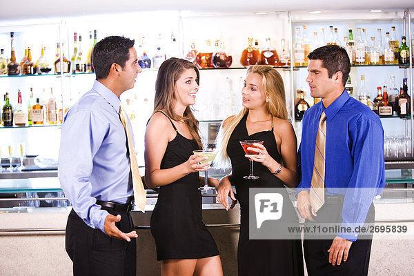 Zwei Mitte erwachsenen Männern und zwei junge Frauen stehen in einer bar