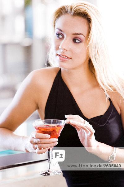 Nahaufnahme einer jungen Frau mit einem Glas martini
