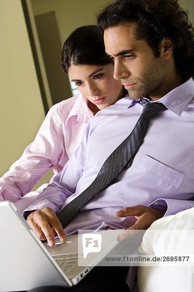 Kaufmann und eine geschäftsfrau an einen laptop