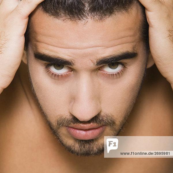 Porträt eines jungen Mannes mit den Händen auf dem Kopf