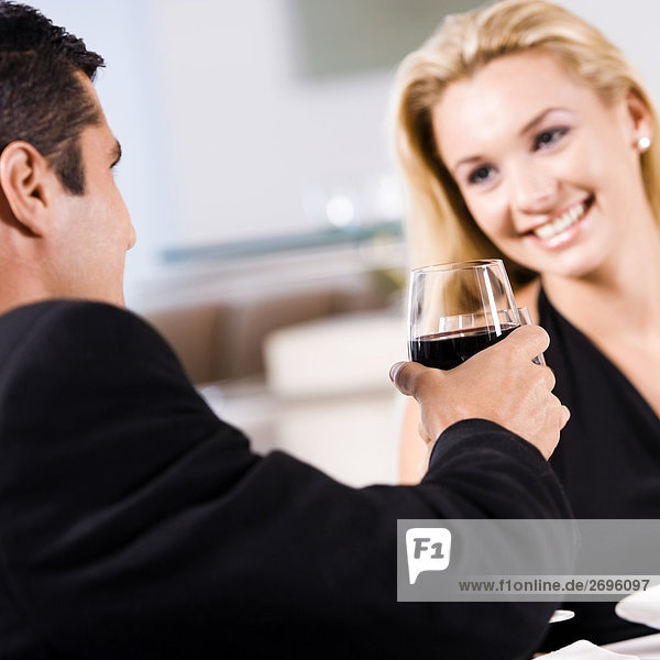 sitzend nebeneinander neben Seite an Seite Frau Mann Glas junger Erwachsener junge Erwachsene halten Rotwein Mittelpunkt jung Erwachsener