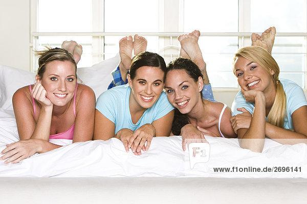 Portrait von vier jungen Frauen liegen Seite an Seite auf einem Bett