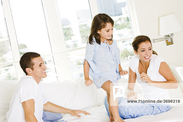Parents and their daughter sitting on the bed