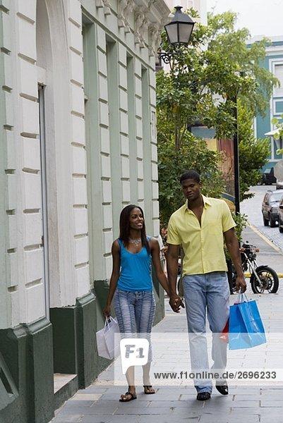 Junger Mann und ein Teenagerin zu Fuß auf dem Gehweg mit Einkaufstaschen