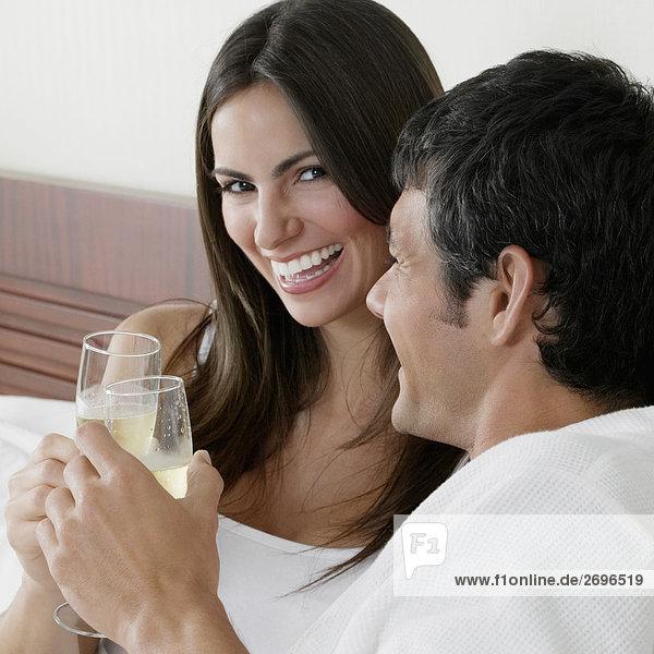 Portrait einer jungen Frau und ein Mitte Erwachsenen Mann toasting with Champagne flutes