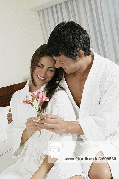 Nahaufnahme eines Mitte erwachsenen Menschen geben Blumen mit einer jungen Frau