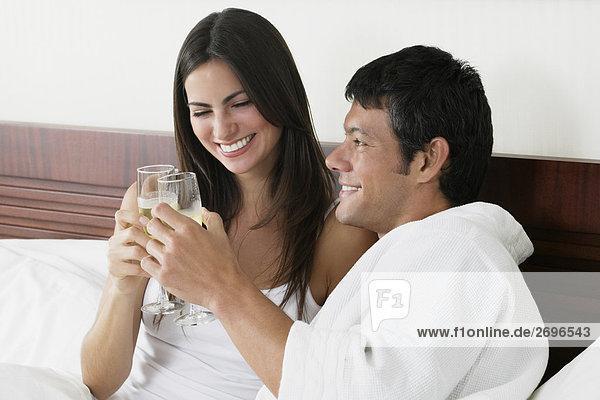 Nahaufnahme einer jungen Frau und ein Mitte Erwachsenen Mann toasting with Champagne flutes