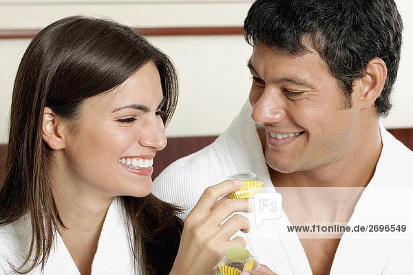 Nahaufnahme of a junge Frau hält ein Cupcake mit einem mittleren erwachsenen Mann Blick auf Ihr