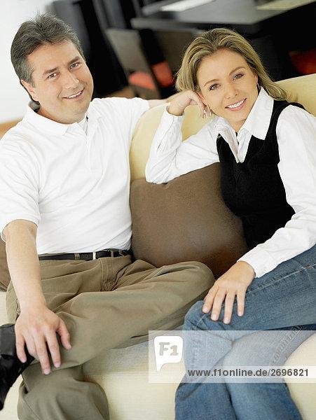 Ein älterer Mann und einer Mitte erwachsen frau sitzt auf einer Couch und lächelnd portrait