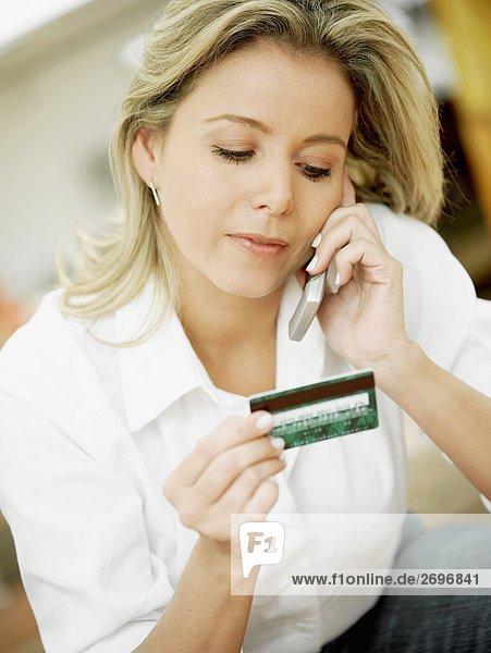 Nahaufnahme einer Mitte erwachsen frau Gespräch auf einem Mobiltelefon und halten eine Kreditkarte