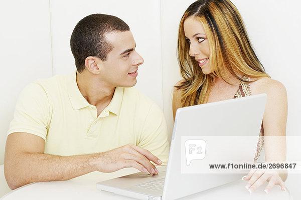Nahaufnahme eines jungen Paares Blick auf einander an einen laptop