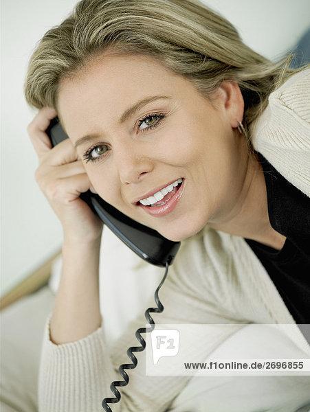 Portrait einer Mitte erwachsen frau sprechen am Telefon und lächelnd