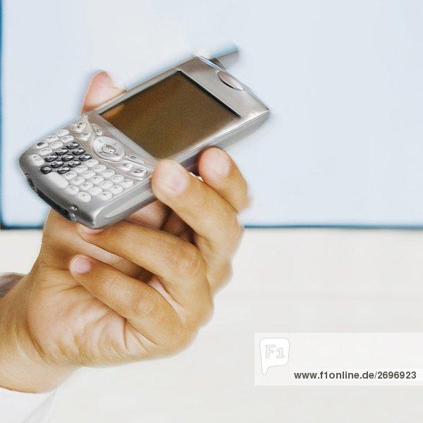 Nahaufnahme die Hand eines Mannes mit einem Mobiltelefon