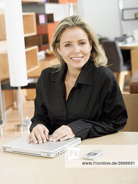 Portrait einer Mitte erwachsen frau mit ihr die Hände auf einem Laptop und lächelnd