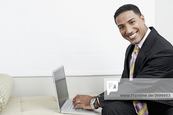 Portrait of a businessman using a laptop and smiling