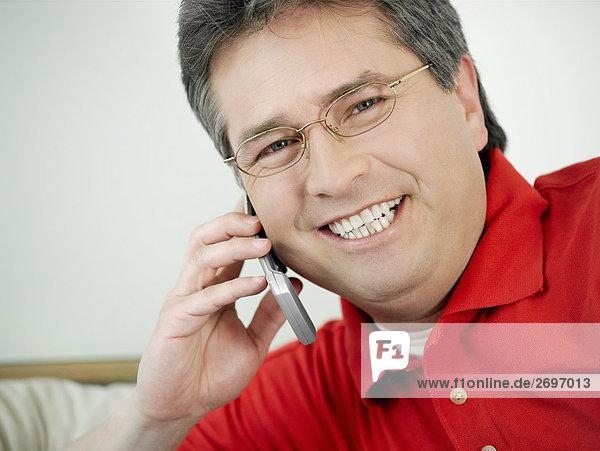 Ein älterer Mann auf einem Mobiltelefon reden und lächelnd portrait
