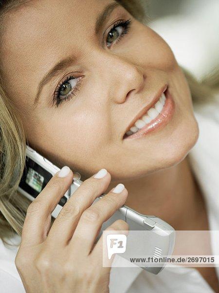 Portrait einer Mitte erwachsen frau Gespräch auf einem Mobiltelefon und lächelnd