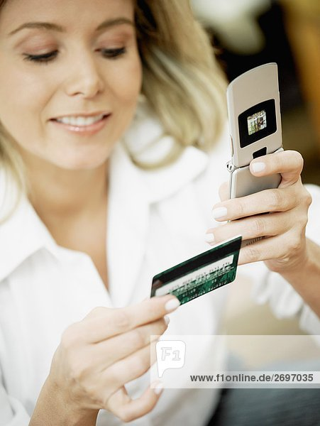 Nahaufnahme einer Mitte erwachsen frau hält ein Handy und eine Kreditkarte