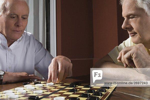 Two senior men playing checkers