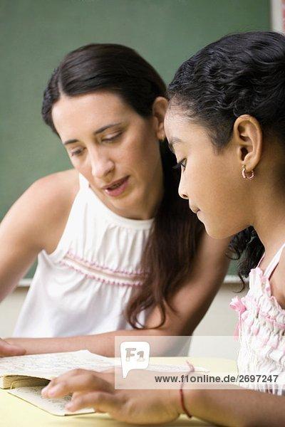 Weibliche Lehrer ihre Schüler in einem Klassenzimmer