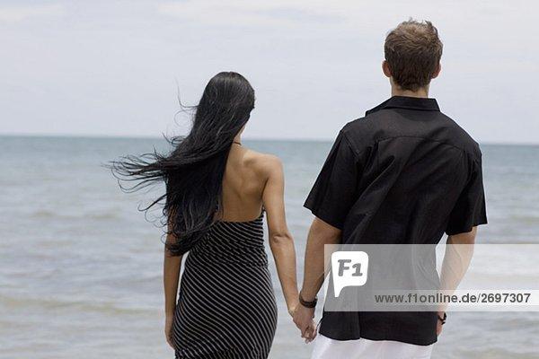 Rückansicht des ein junges paar steht am Strand