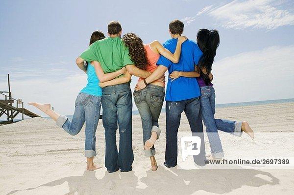 Rückansicht von fünf Personen stehen am Strand