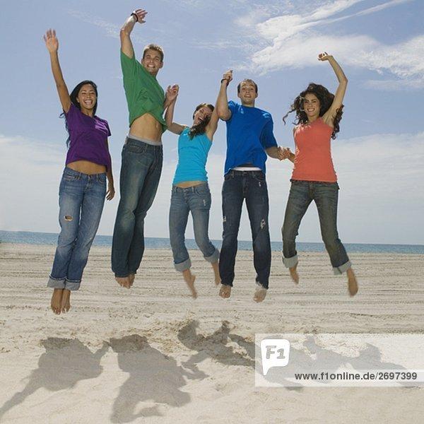 Portrait von fünf jungen Menschen springen am Strand