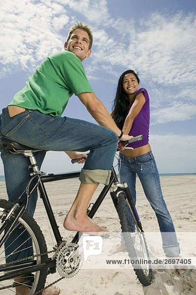 Nahaufnahme eines jungen Mannes auf einem Fahrrad mit einer jungen Frau neben ihm sitzt