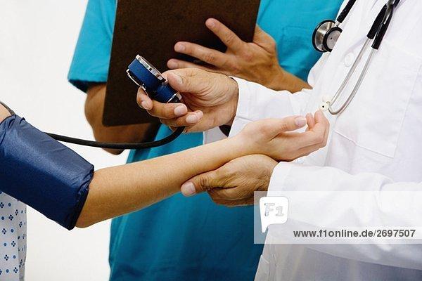 Mitte Schnittansicht der männlichen Arzt messen Blutdruck eines weiblichen Patienten