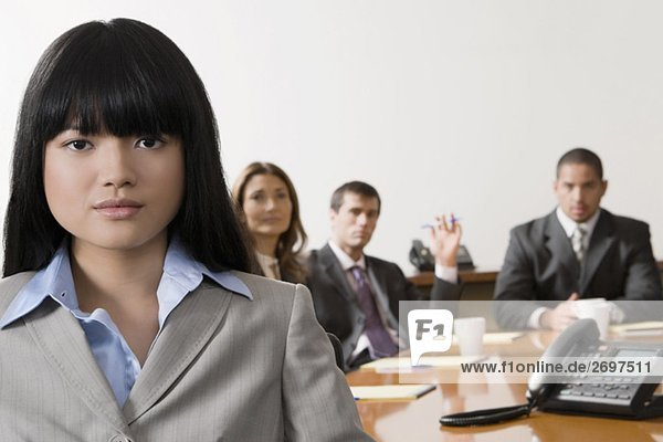 Porträt von lächelnd mit anderen Führungskräften in einem Sitzungssaal geschäftsfrau