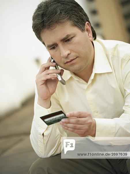 Nahaufnahme ein älterer Mann auf einem Mobiltelefon reden und halten eine Kreditkarte