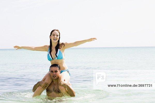 Porträt eines Mitte Erwachsenen Mannes tragen eine junge Frau auf seinen Schultern im Meer