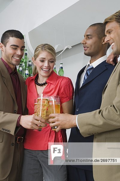 Four business executives toasting with glasses of beer in a party