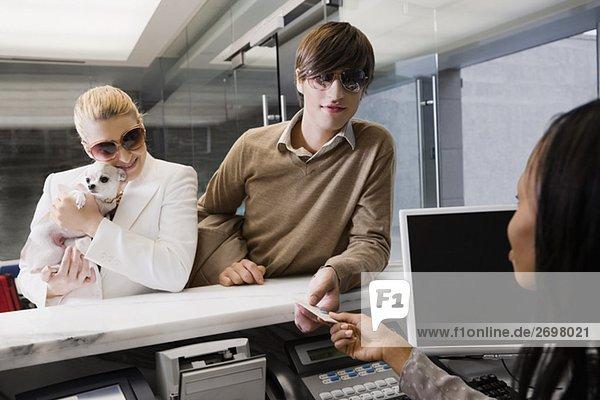 Junger Mann geben eine Kreditkarte an der Rezeption