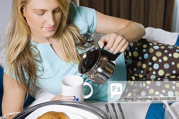 Junge Frau Gießen Tee in eine Teetasse