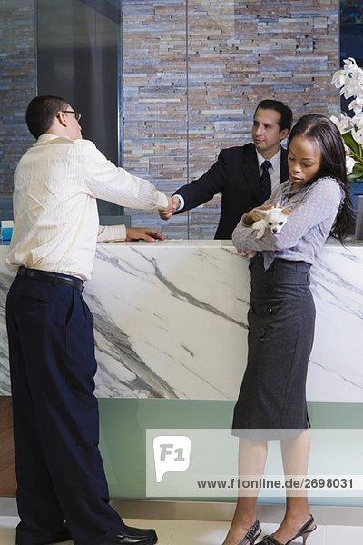 Junger Mann Händeschütteln mit Empfangsdame und eine junge Frau hält ein Welpe