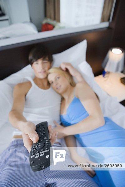 Erhöhte Ansicht eines jungen Paares auf dem Bett liegend und Fernsehen